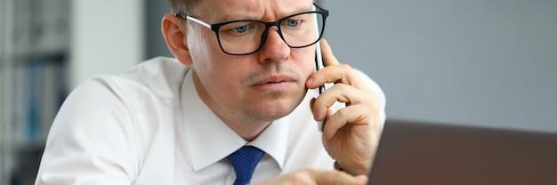 Mężczyzna mówi przez telefon i wskazuje na ekran komputera