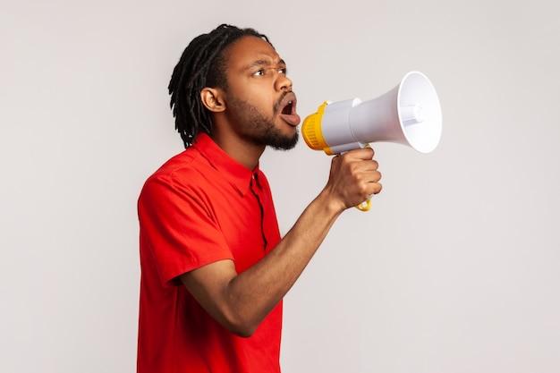 Mężczyzna mówiący trzymający głośnik przy ustach, mówiący o nowych ważnych informacjach