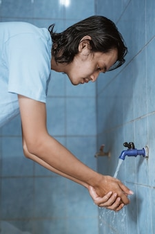 Mężczyzna muzułmanin wykonuje ablucję (wudhu), myjąc ręce przed modlitwą