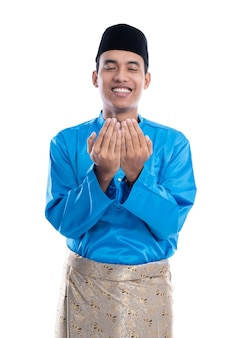 Mężczyzna muzułmanin z czapką modląc się do boga na białym tle