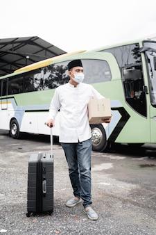 Mężczyzna muzułmański podróżujący publicznym autobusem podczas pandemii noszący maskę
