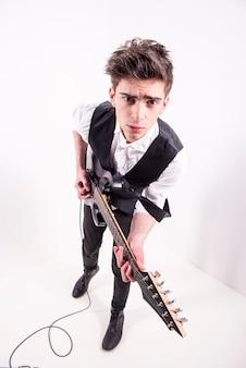 Mężczyzna muzyk gra w studiu na sześciostrunowej gitarze basowej.