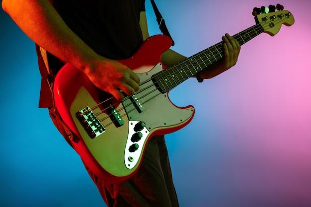 Mężczyzna muzyk grający na gitarze na neonowym świetle
