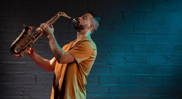 Mężczyzna muzyk grający na saksofonie w świetle reflektorów z miejsca na kopię
