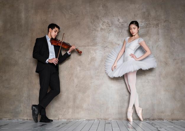 Mężczyzna muzyk grający na skrzypcach dla baleriny