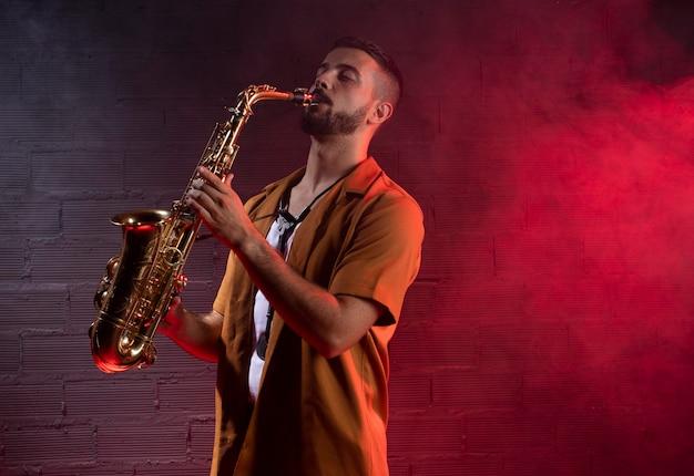 Mężczyzna muzyk we mgle gra na saksofonie