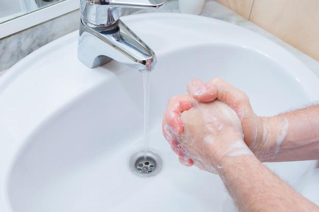 Mężczyzna mycia rąk mydłem pod umywalką w łazience. zbliżenie dezynfekcja rąk i leczenie koronawirusa.