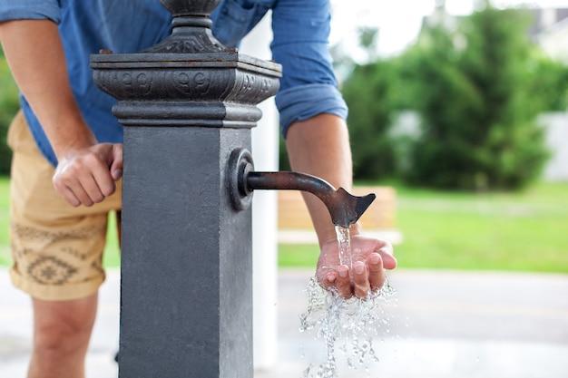 Mężczyzna mycia rąk w wodzie z kranu w parku