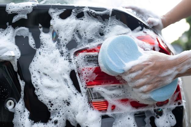 Mężczyzna myjący czarny samochód niebieską gąbką