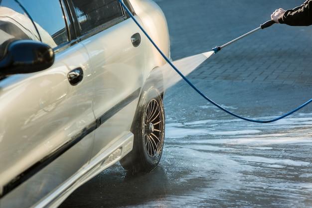 Mężczyzna myjący samochód strumieniem wody w samoobsługowej myjni samochodowej, zbliżenie