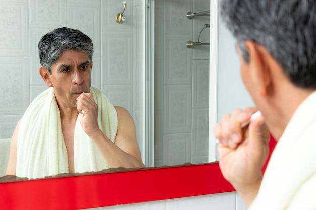 Mężczyzna myjący zęby po prysznicu