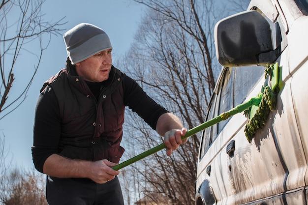Mężczyzna myje biały, brudny samochód na zewnątrz.