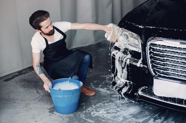 Mężczyzna myje jego samochód w garażu