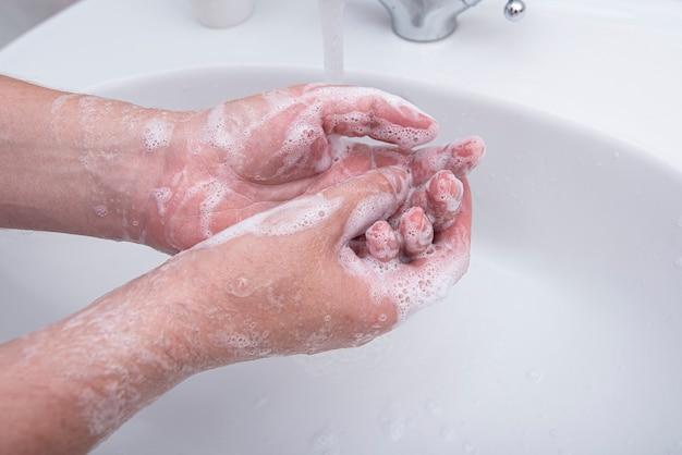 Mężczyzna myje ręce mydłem z pianką, obraz koncepcyjny dotyczący wirusów i higieny