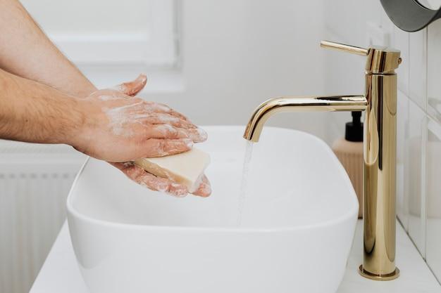 Mężczyzna myje ręce mydłem