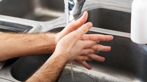 Mężczyzna myje ręce w metalowym zlewie za pomocą mydła. kaukaski mężczyzna umyć ręce. higiena rąk, opieka zdrowotna, dezynfekcja koncepcja medyczna. dezynfekcja skóry rąk chroni przed coronavirus covid 19. długi baner internetowy