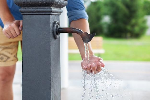 Mężczyzna myje ręce w wodzie z kranu z wodą w parku. kolumna do picia