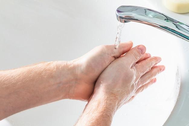 Mężczyzna myje ręce w zlewie