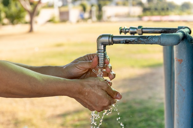 Mężczyzna myje ręki od instalaci wodnokanalizacyjnej klepnięcia plenerowego.
