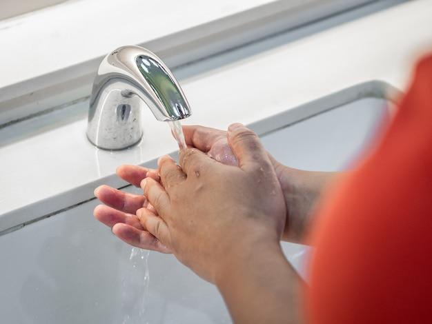Mężczyzna myje ręki pod kranem