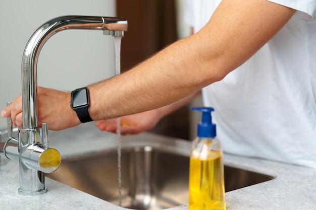 Mężczyzna myje ręki z mydłem w zlew w jego domu