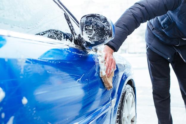 Mężczyzna myje samochód myjką. myjnia samoobsługowa