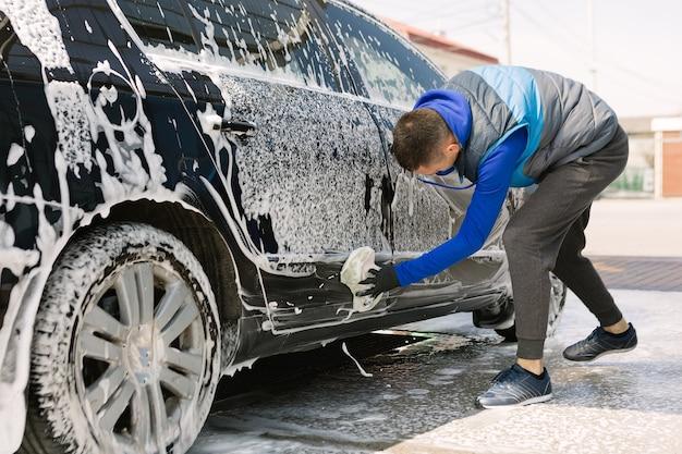 Mężczyzna myje samochód na myjni samoobsługowej. ekspresowa myjnia samochodowa