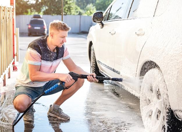 Mężczyzna myje samochód w samoobsługowej myjni samochodowej
