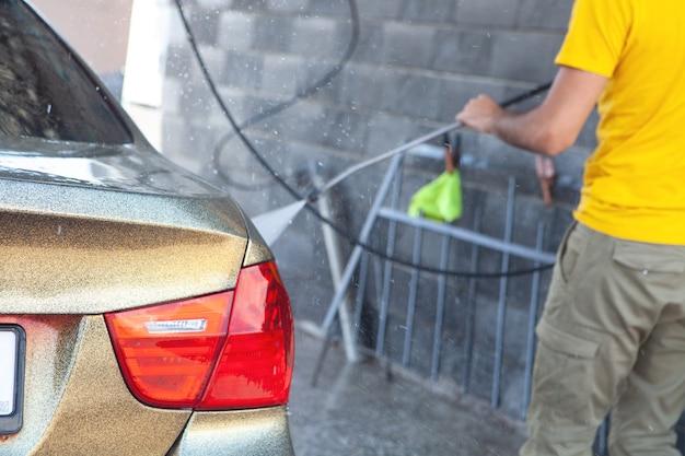 Mężczyzna myje samochód wodą