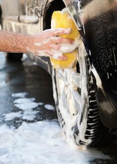 Mężczyzna myje samochód z mydłem żółtą gąbką.