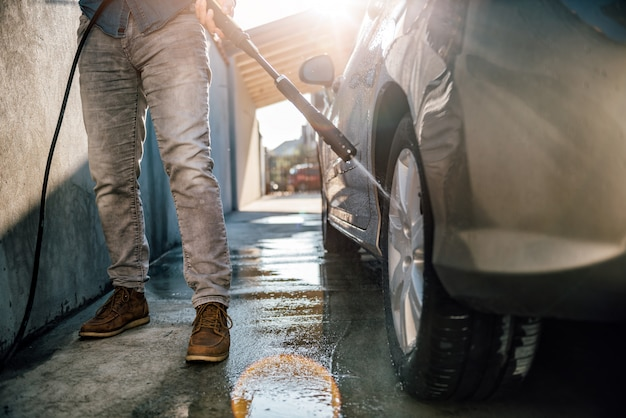 Mężczyzna myje swój samochód myjką ciśnieniową