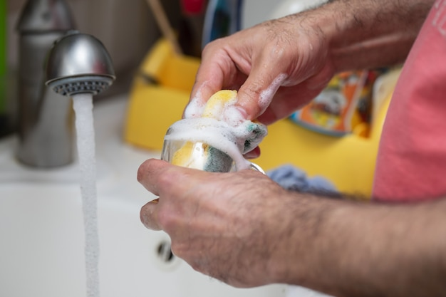 Mężczyzna myje szklany kubek w kuchni