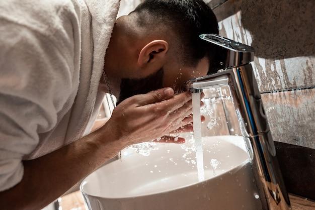 Mężczyzna myje twarz w umywalce w łazience