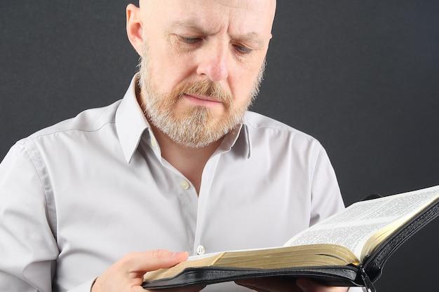 Mężczyzna myśli o czytaniu książki biblijnej