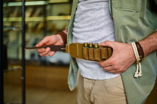 Mężczyzna myśliwy kupujący skórzany bandolier w sklepie z bronią