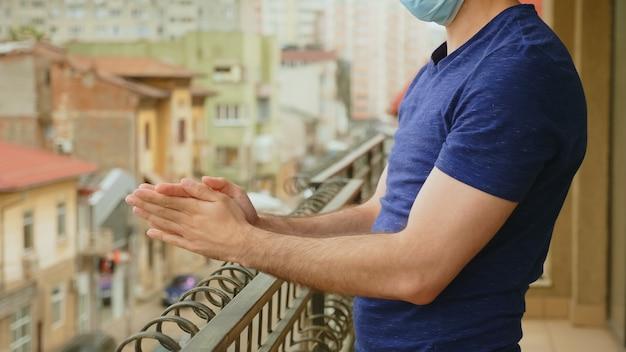 Mężczyzna na balkonie klaszczący w poparciu dla lekarzy podczas globalnej blokady pandemicznej