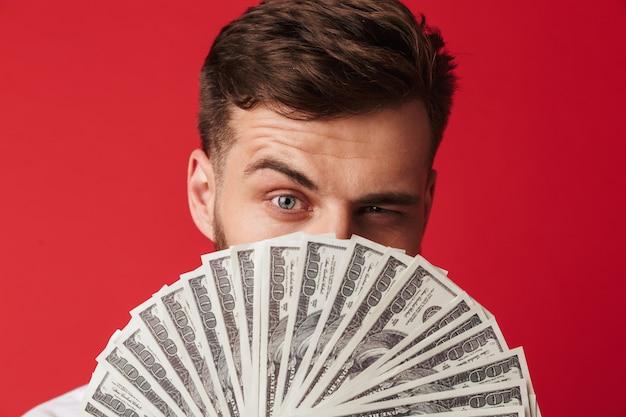 Mężczyzna na białym tle nad czerwoną ścianą, trzymając pieniądze obejmujące twarz.