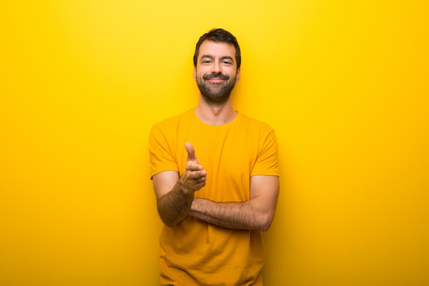 Mężczyzna na białym tle tętniącego życiem żółty kolor wytrząsanie rąk do zamknięcia dobrej oferty