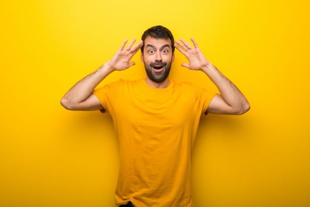 Mężczyzna na białym tle tętniącego życiem żółty kolor z niespodzianką i zszokowany wyraz twarzy