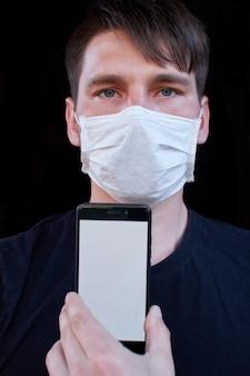 Mężczyzna na ciemnej ścianie w masce medycznej. ochrona przed wirusami, bakteriami i chorobami
