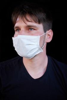 Mężczyzna na ciemnym tle w masce medycznej. ochrona przed wirusami, bakteriami i chorobami