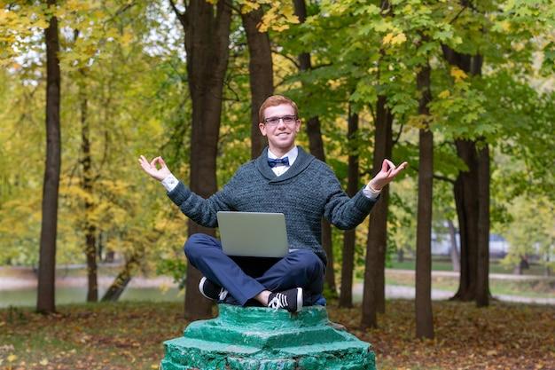 Mężczyzna na cokole udający posąg medytuje w parku w pozycji lotosu