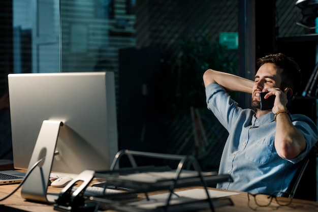 Mężczyzna na czacie przez telefon w ciemnym biurze
