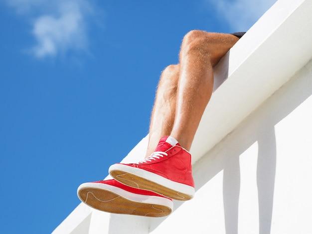 Mężczyzna na dachu w stylowych czerwonych tenisówkach z białymi sznurowadłami. widok opalonych nóg.