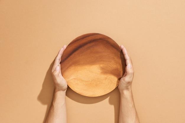 Mężczyzna na dwie ręce trzyma puste naczynie na beżu