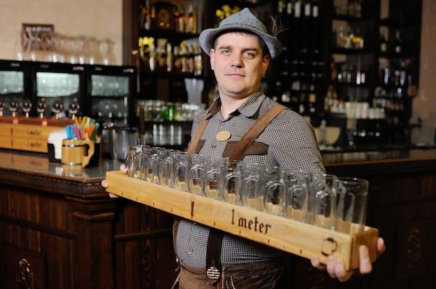 Mężczyzna na festiwalu oktoberfest w tradycyjnych bawarskich strojach i czapce trzyma metr piwa i uśmiecha się
