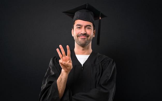 Mężczyzna na jego ukończeniu uniwersytet szczęśliwy i licząc trzy palce na czarnym tle