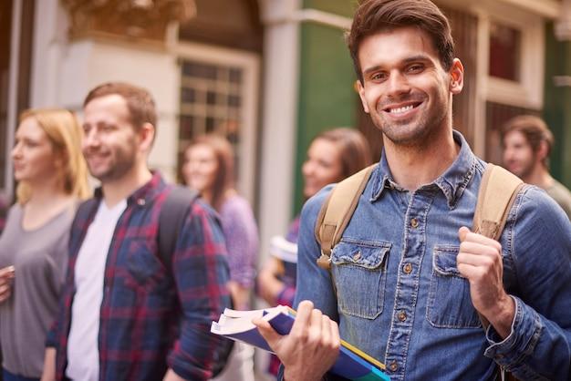 Mężczyzna na kampusie uniwersyteckim z kolegami