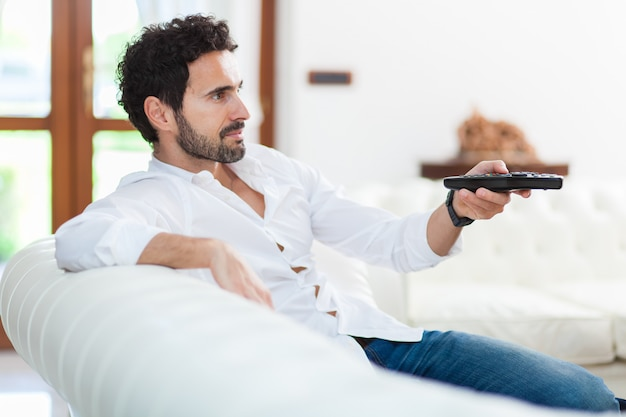 Mężczyzna na kanapie przełącza kanały telewizyjne na pilocie