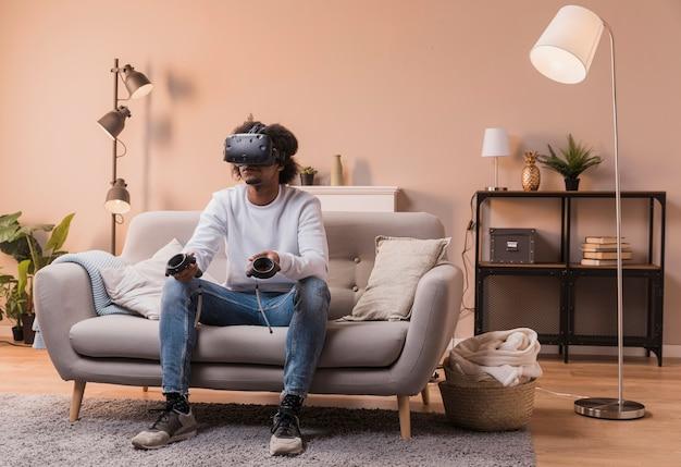 Mężczyzna na kanapie z wirtualnym zestawem słuchawkowym